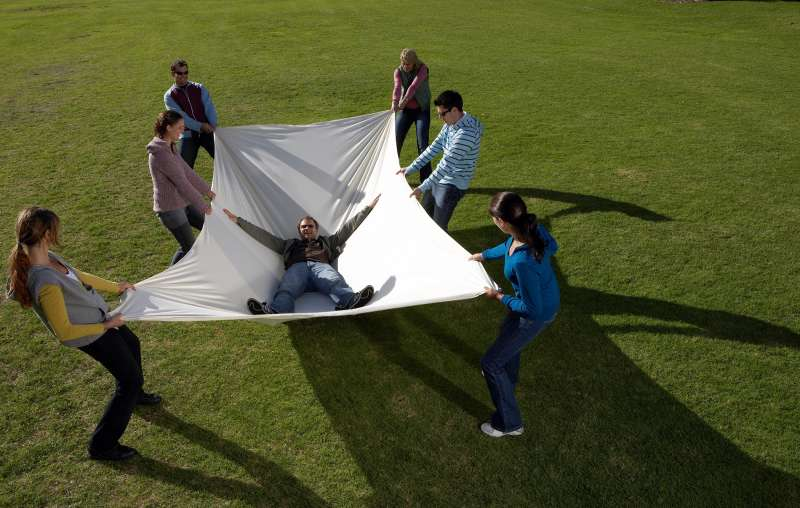 people catching a man in a sheet after a trust fall