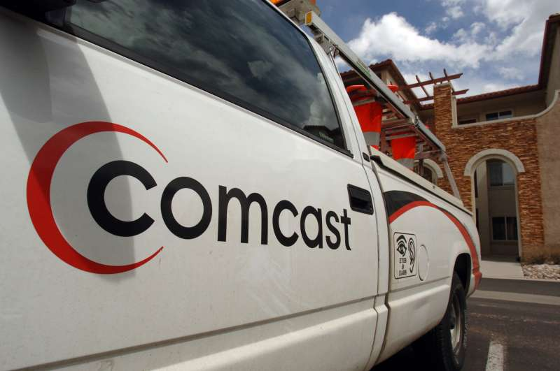 The Comcast logo is pictured on the side of a truck sitting