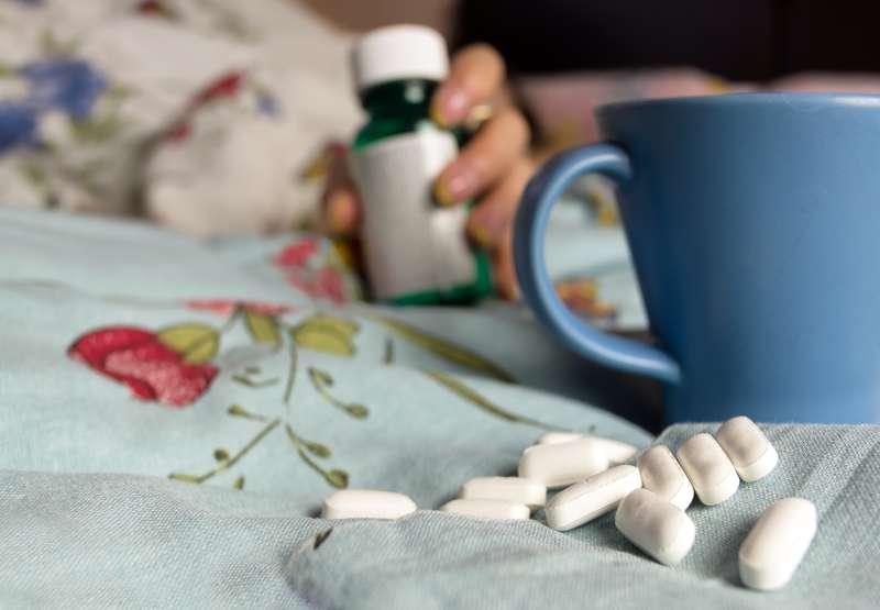 pills, medicine and mug of tea on bed blanket