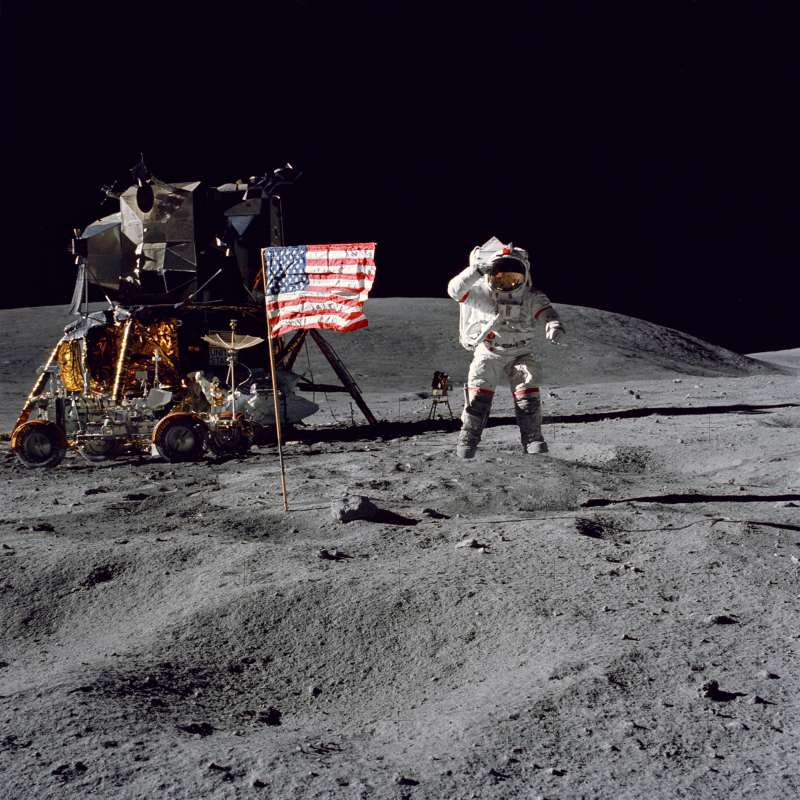 Astronaut John W. Young, commander of the Apollo 16 lunar landing mission, leaps from the lunar surface as he salutes the United States flag at the Descartes landing site near Stone Mountain during the first Apollo 16 extravehicular activity (EVA), April 16, 1972. The Lunar Module  Orion  is at the left with the Lunar Roving Vehicle is parked beside it.