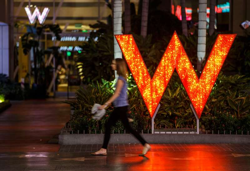 A woman walks past signage displayed outside of the W Hotel Hollywood in Hollywood, California, on October 26, 2015.