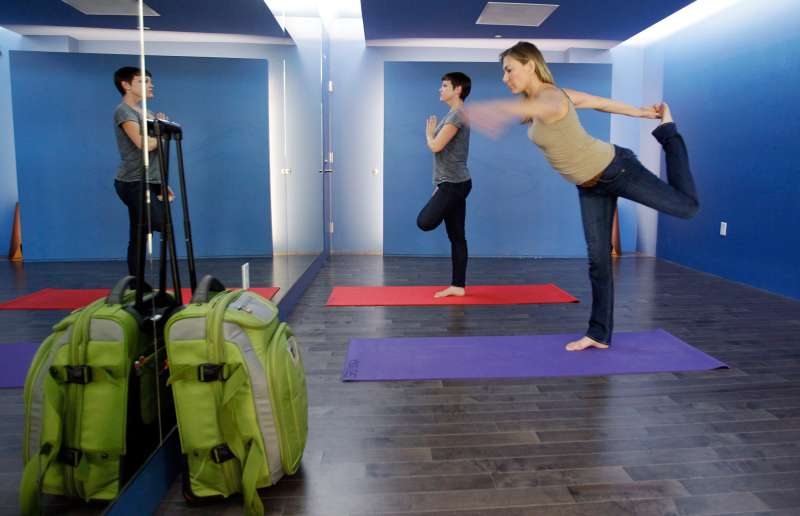 In this January 27, 2012 photo, travelers Maria Poole, right, and Lindsey Shepard, practice yoga at San Francisco International Airport's new Yoga Room, in San Francisco. The quiet, dimly lit studio officially opened last week in a former storage room just past the security checkpoint at SFO's Terminal 2. Airport officials believe the 150-square-foot room with mirrored walls is the world's first airport yoga studio, said spokesman Mike McCarron.
