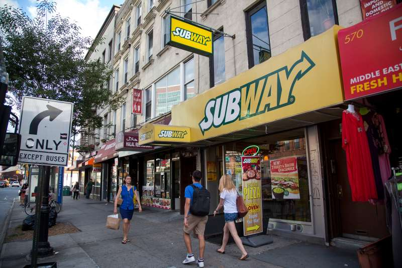 Pedestrians pass a Subway restaurant on Atlantic Avenue in Brooklyn, U.S., on Thursday, August 27, 2015.  Photographer: Michael Nagle/Bloomberg