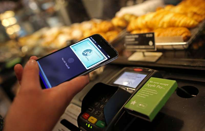 A customer uses an Apple iPhone to pay via the Apple Pay system, from their American Express Co., account, at the check-out till inside a Pret A Manger store in in London, on  July 14, 2015.