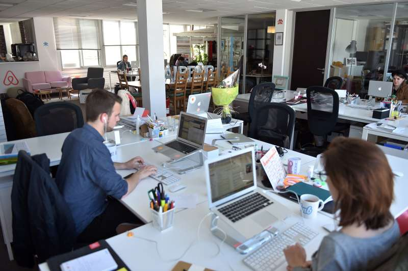 Employees of online lodging service Airbnb work in the Airbnb offices in Paris on April 21, 2015.