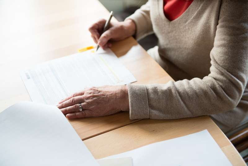senior filling out paperwork