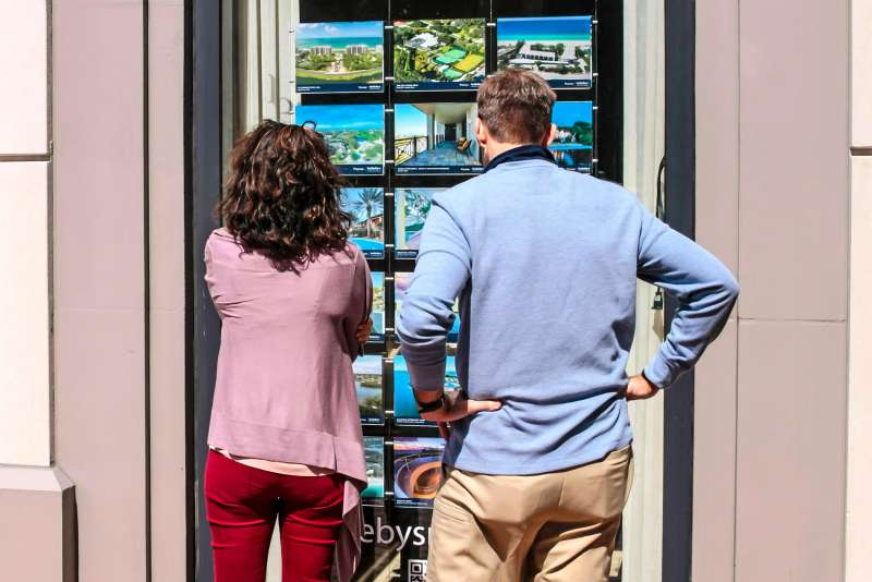 A couple looks at a window display of homes for sale outside a real estate brokers office in Sarasota, Florida, February 21, 2015.
