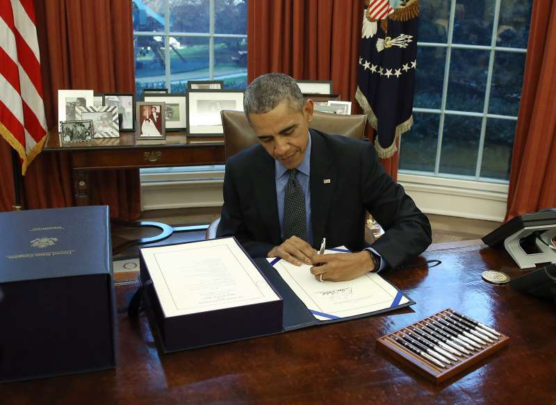 U.S. President Barack Obama signs the budget bill that will fund the government until next September, in the Oval Office at the White House December 18, 2015 in Washington, DC.