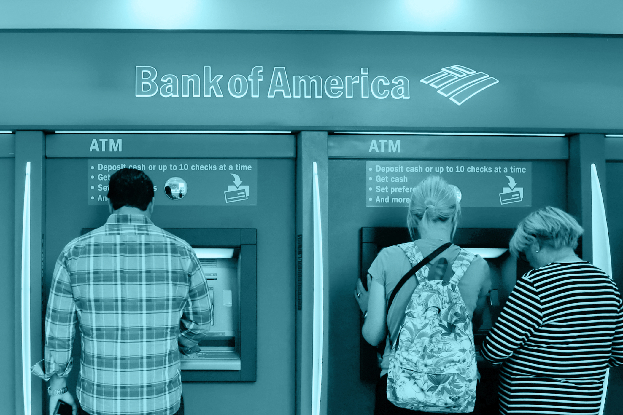 In this photo taken, July 13, 2015, customers use ATMs at a branch office of Bank of America in New York.