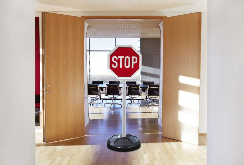 stop sign in front of the doors to a meeting room