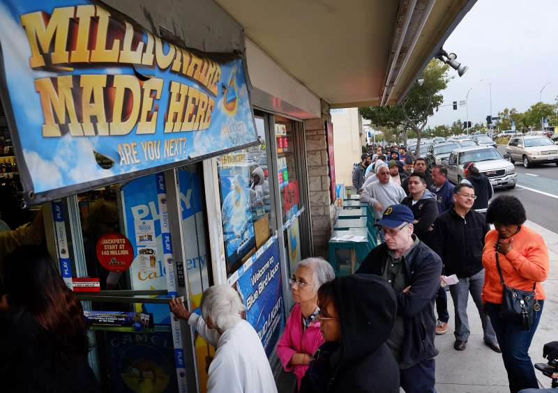 Customers wait in line at the Blue Bird Liquor Store to buy Powerball lottery tickets in Hawthorne, California on January 9, 2016.