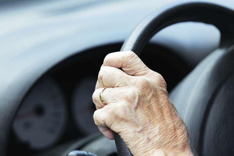 senior hand on steering wheel