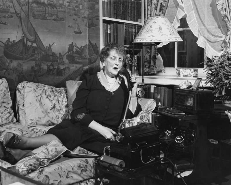 Writer Emily Post (1872-1960) pictured in her living room speaking on the telephone, USA, circa 1940. An author on the subject of etiquette, Post founded the Emily Post Institute in 1946, an organisation providing etiquette experts and advice.