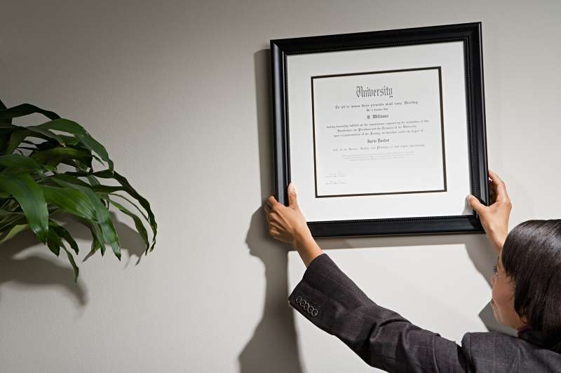 woman hanging diploma in office