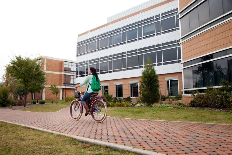 girl riding bicycle on campus