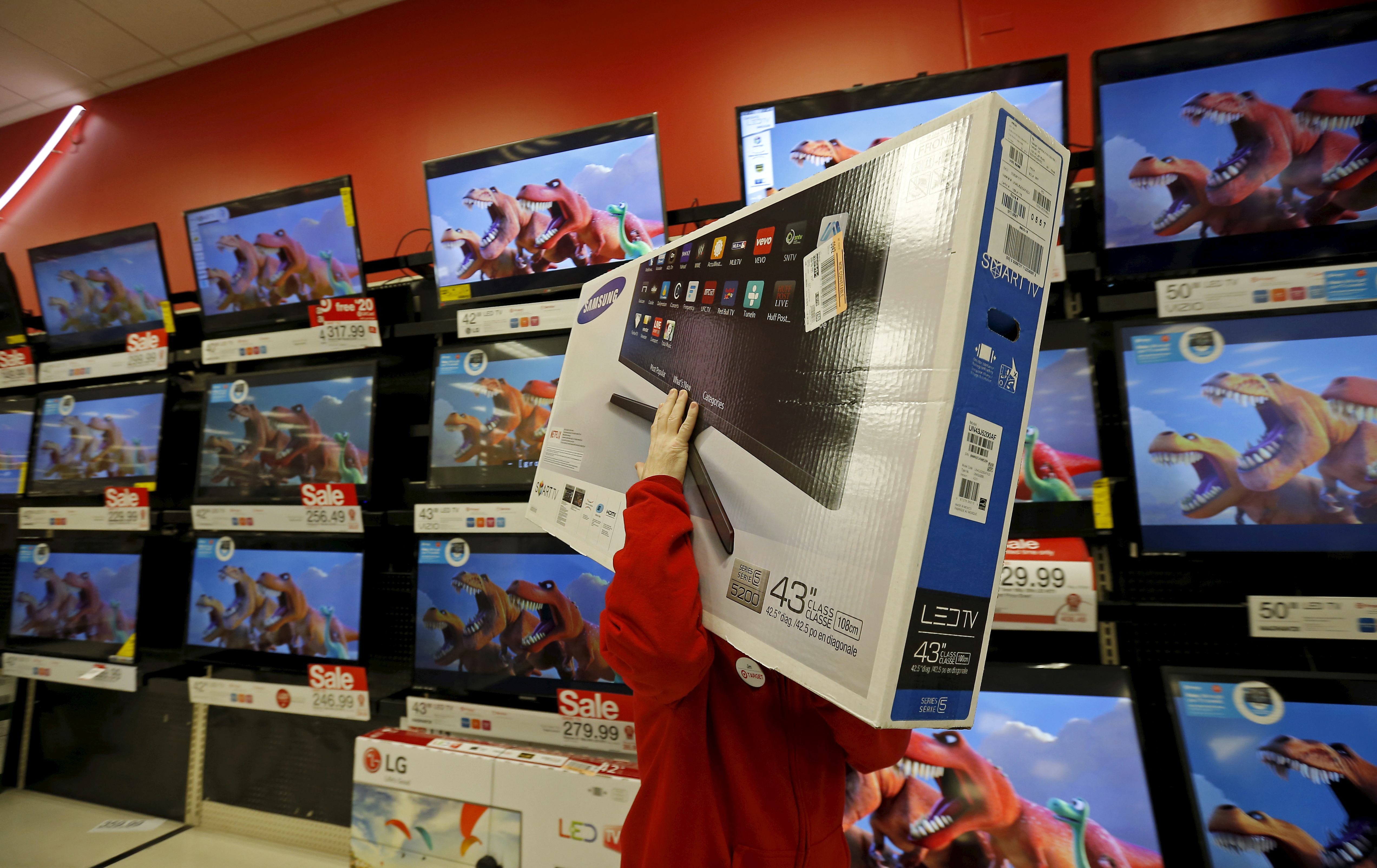 A worker carries a television for a customer who made a purchase during Black Friday Shopping at a Target store in Chicago, Illinois, November 27, 2015.