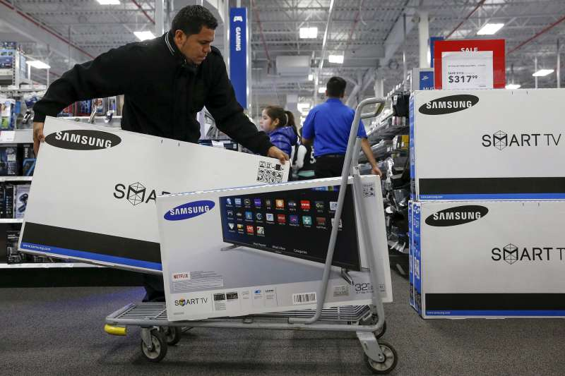 A shopper puts televisions on a shopping cart at a Best Buy store in Westbury, New York November 27, 2015.