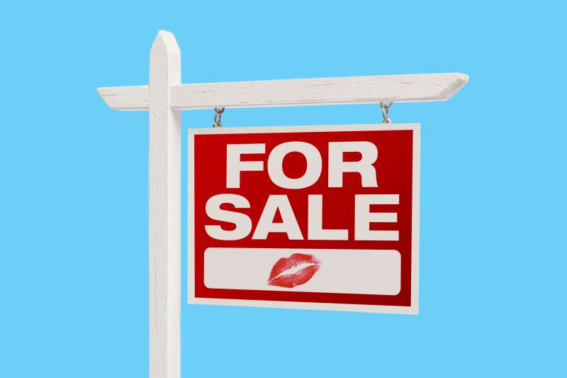 Home For Sale sign with lipstick mark