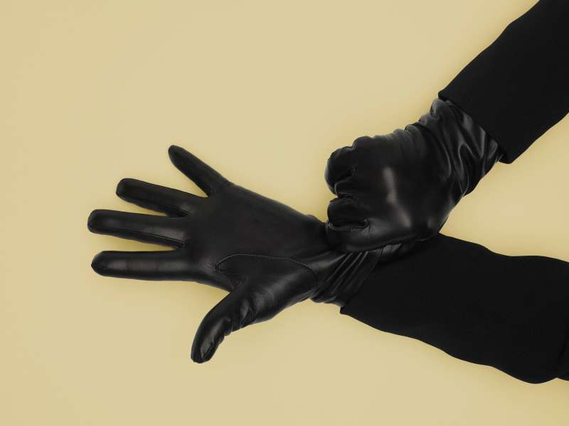 Mature woman adjusting leather gloves, close-up of hands