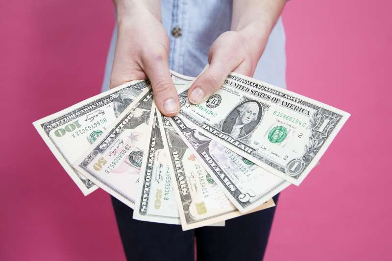 woman holding fan of money