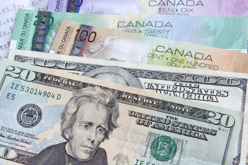 american dollars on top of canadian dollars