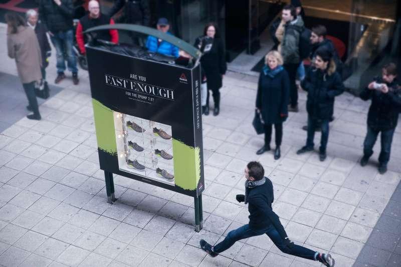 man running past reebok ad