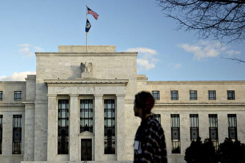 A pedestrian walks past the Marriner S. Eccles Federal Reserve building in Washington, D.C., U.S., on December 15, 2015.