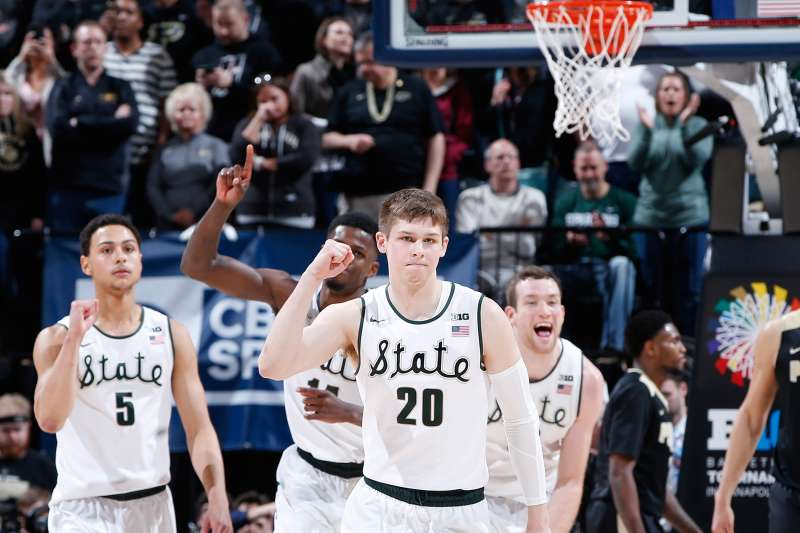 The Michigan State Spartans celebrate after defeating the Purdue Boilermakers in the championship game of the Big Ten Basketball Tournament at Bankers Life Fieldhouse on March 13, 2016 in Indianapolis, Indiana. Michigan State defeated Purdue 66-62.
