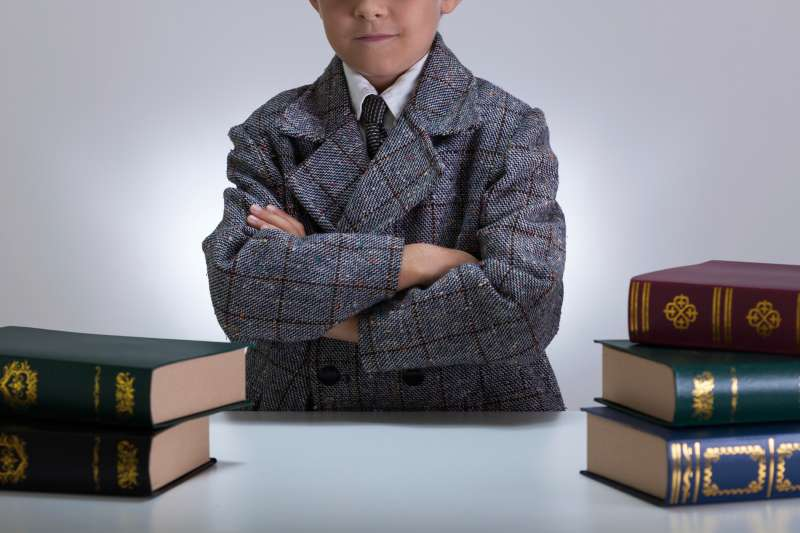 little boy dressed in suit with encyclopedias