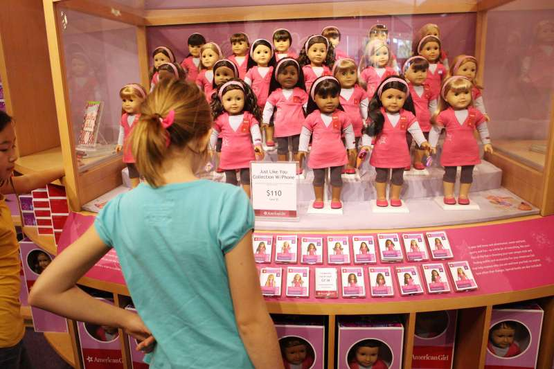 Girls look at dolls on display at the American Girl store in Los Angeles.