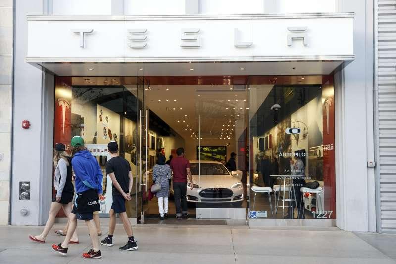 Pedestrians walk past the Tesla Motors Inc. showroom at the Third Street Promenade in Santa Monica, California, on March 22, 2016.