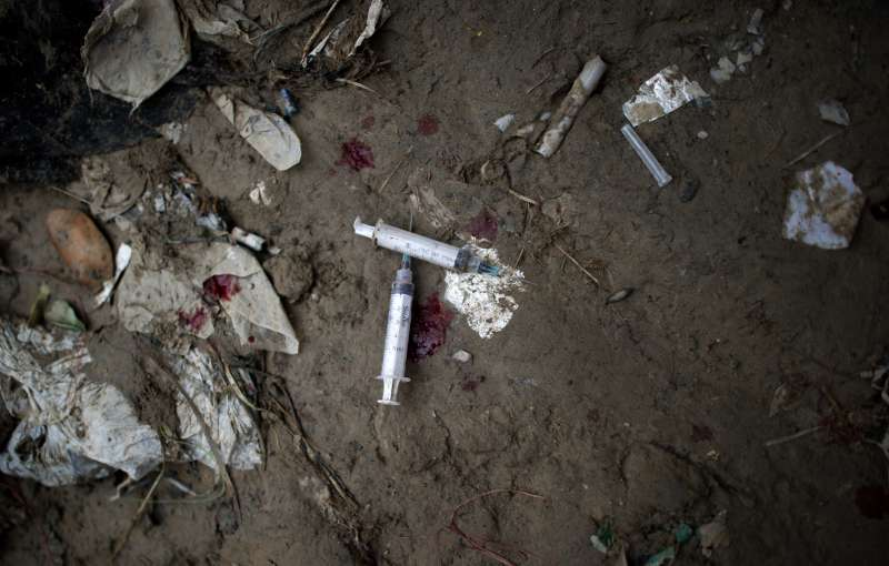 Blood and two heroin syringes are pictur