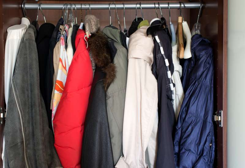Various clothes, leather jacket with fur collar hanging in the wardrobe