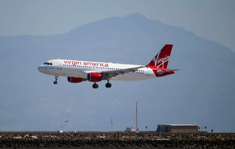 A Virgin America plane lands at San Francisco International Airport on March 29, 2016 in Burlingame, California. JetBlue Airways and Alaska Air Group are reportedly preparing takeover offer bids for Virgin America airlines.