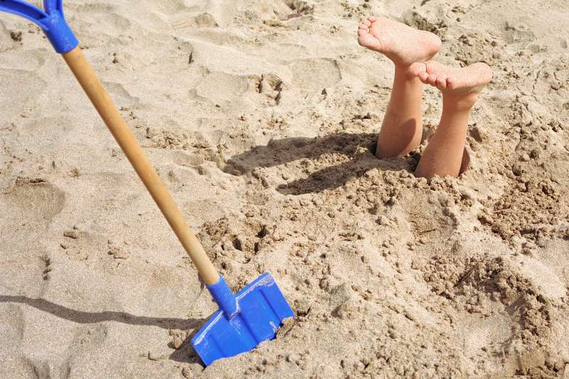 Buried on beach, feet sticking out of sand