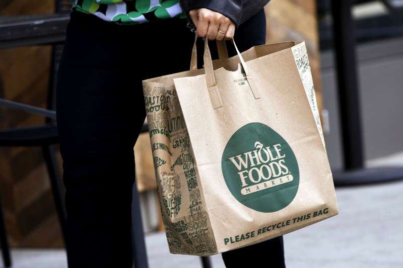 A customer carries a shopping bag outside the new Whole Foods Market Inc. store in downtown Los Angeles, on Nov. 9, 2015.