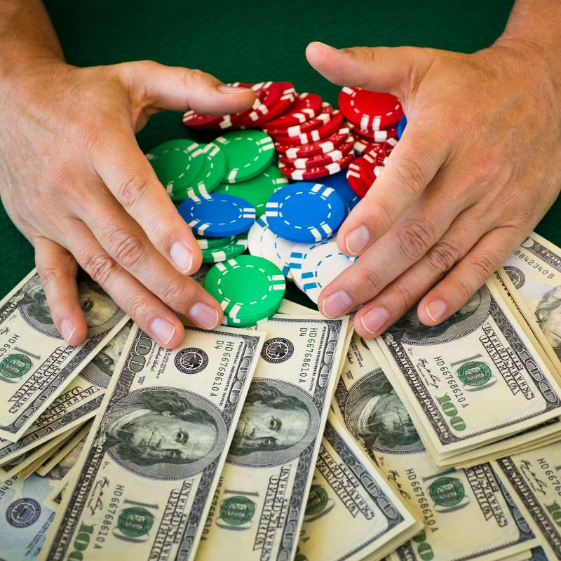 person collecting poker chip and money winnings