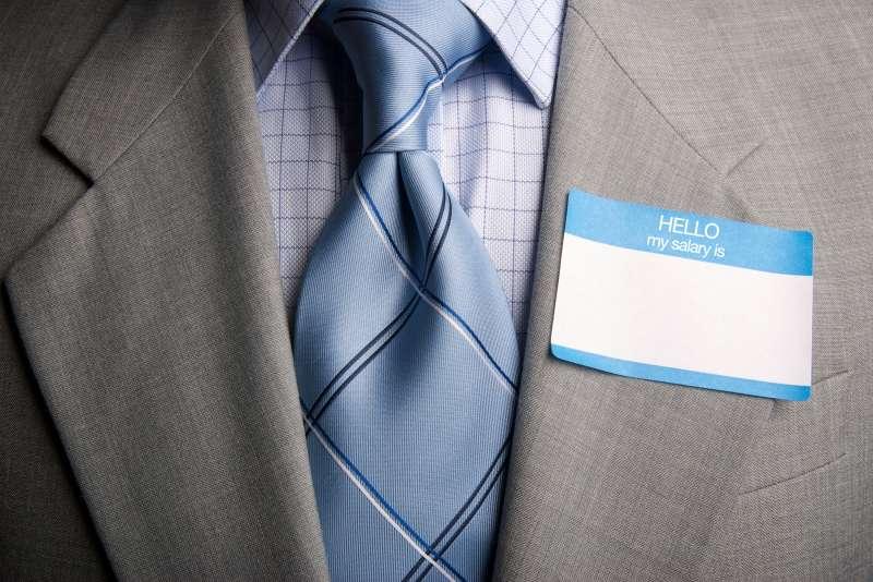 man wearing  HELLO my salary is  sticker on suit