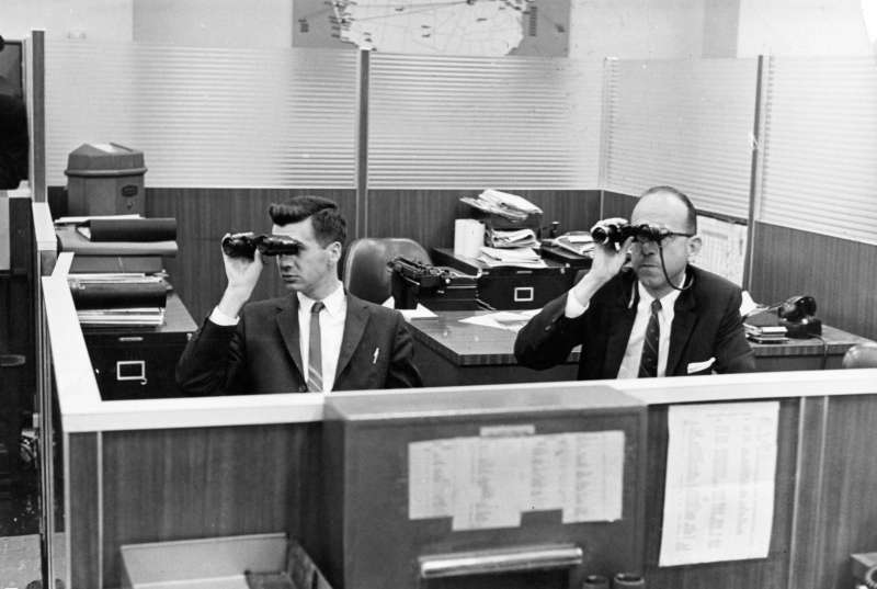 Two men in a New York Stock Exchange office use binoculars, circa 1962.