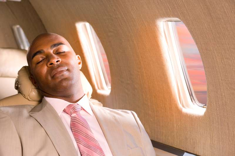 Businessman sleeping in airplane