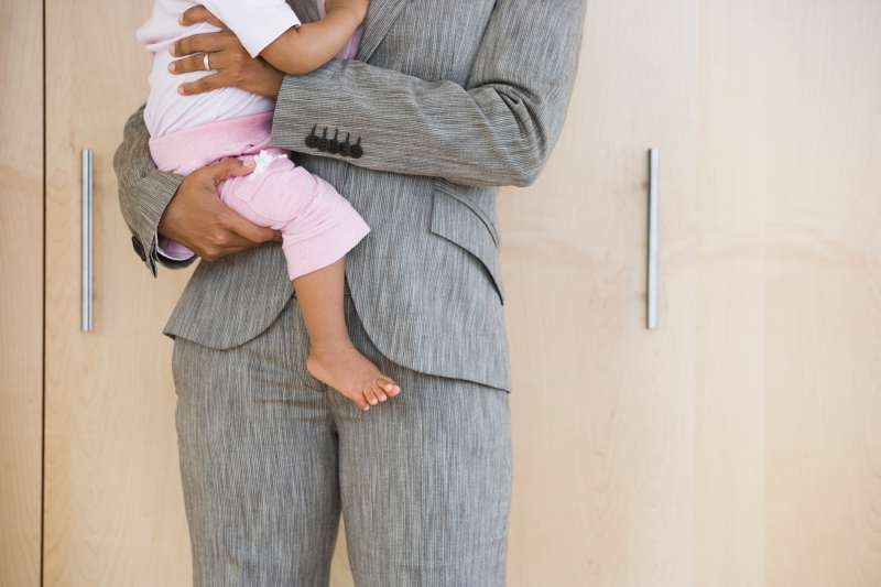woman in business suit holding baby