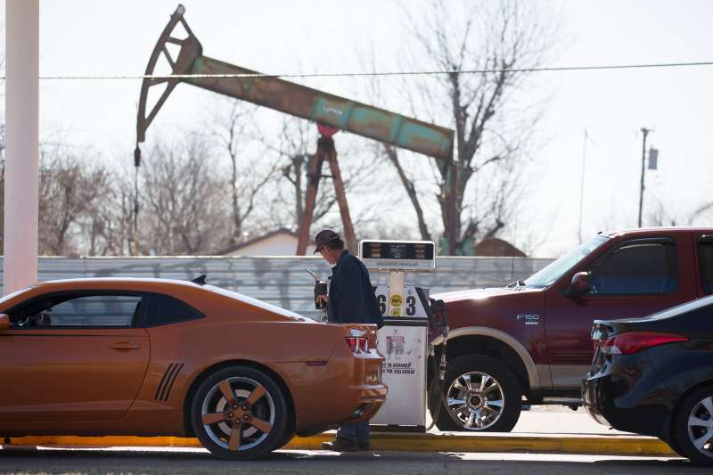 A motorist fills his car with gas at a gas station near an oil field pumping rig in Oklahoma City, Feb. 12, 2016.
