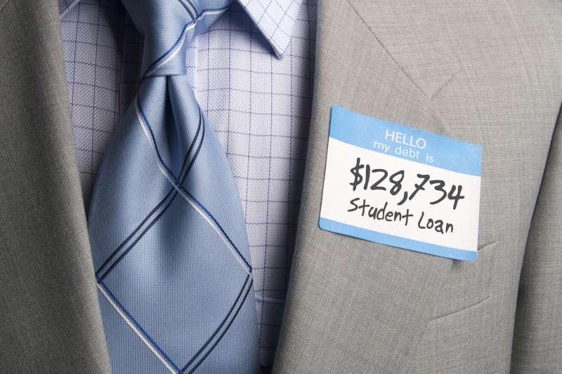 man in suit wearing  hello my debt is....$128,734 Student Loan  sticker