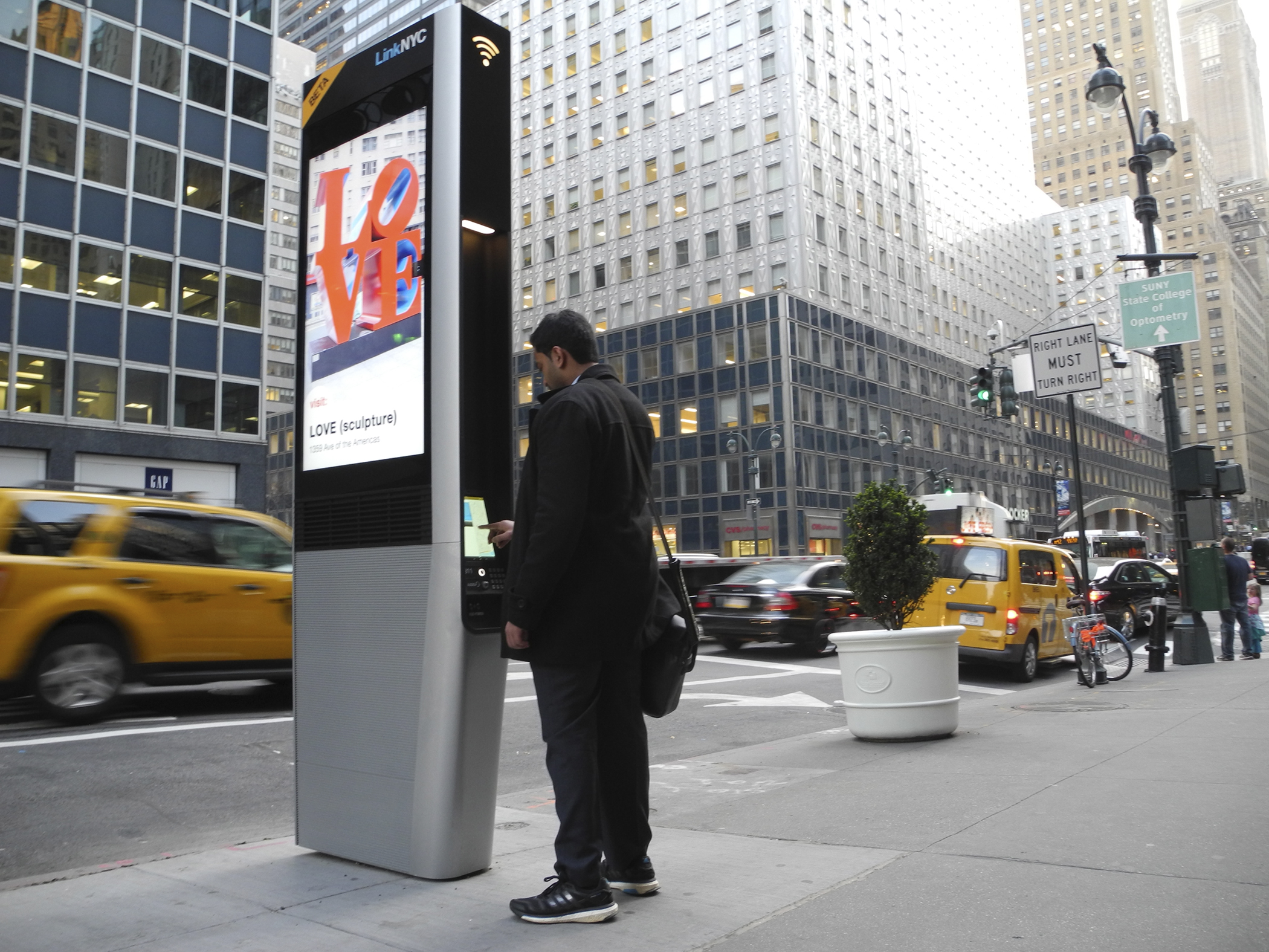 A man uses a LinkNYC station in New York, USA, 23 March 2016. These stations offer free Wi-Fi in the city.