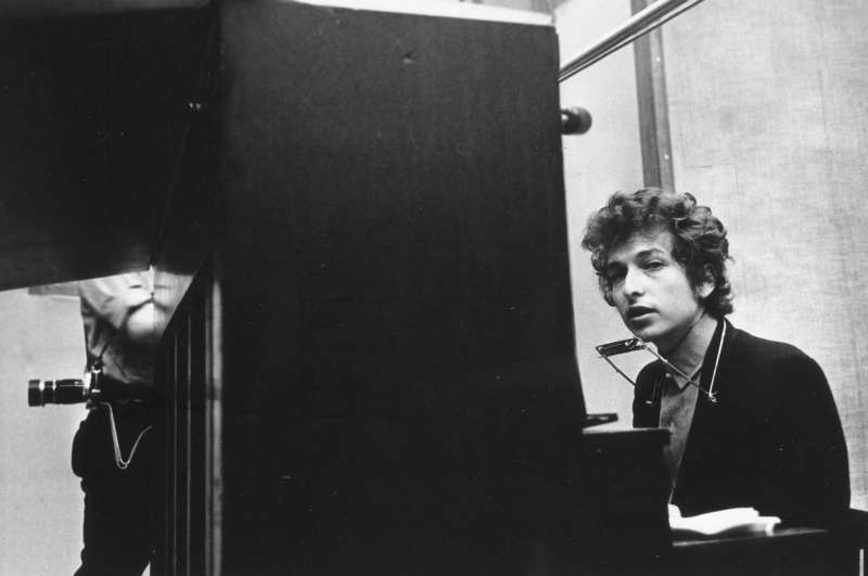 Bob Dylan (seated at the piano with a harmonica around his neck) takes a break during the recording of the album 'Highway 61 Revisited' in Columbia's Studio A in the summer of 1965 in New York City, New York.