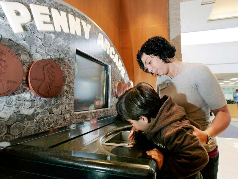 In this April 11, 2009 photo, three-year-old Charlie Cala gets help from TD Bank employee Lisa Louden as he loads his change into the bank's Penny Arcade coin counting machine at a TD Bank branch in Fairless Hills, Pa. TD Bank offers free coin turn-ins at its Penny Arcade machines, regardless of whether you're a customer.