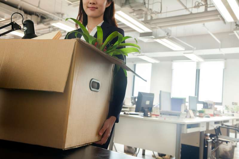 woman carrying box out of office