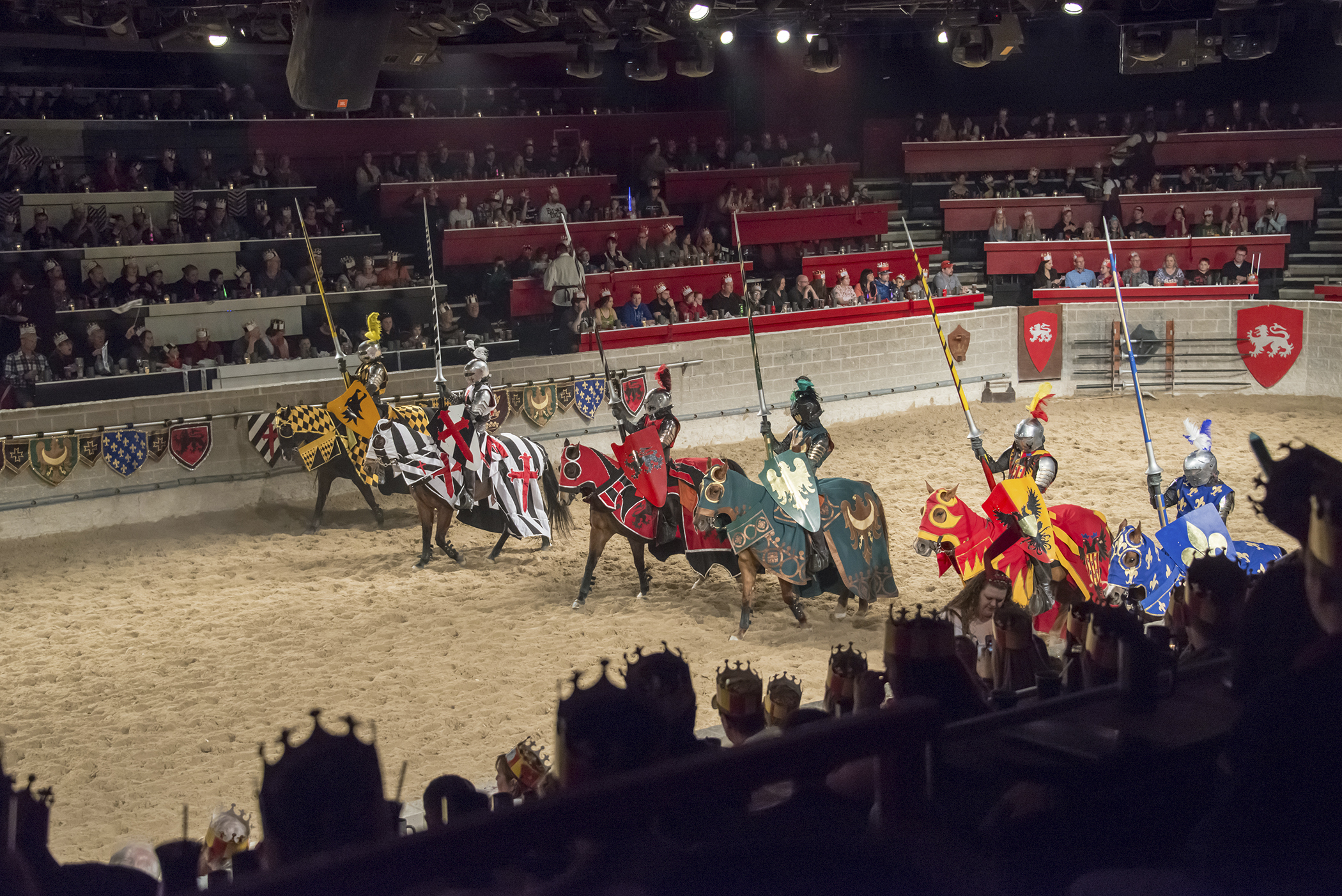 Medieval Times Restaurant: Six horsemen at a jousting event, dressed as medieval knights holding lances, lined up in a stadium full of spectators, waiting to begin the show, Toronto, Ontario, March 21, 2015.