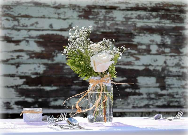 mason jar of flowers on table at rustic wedding
