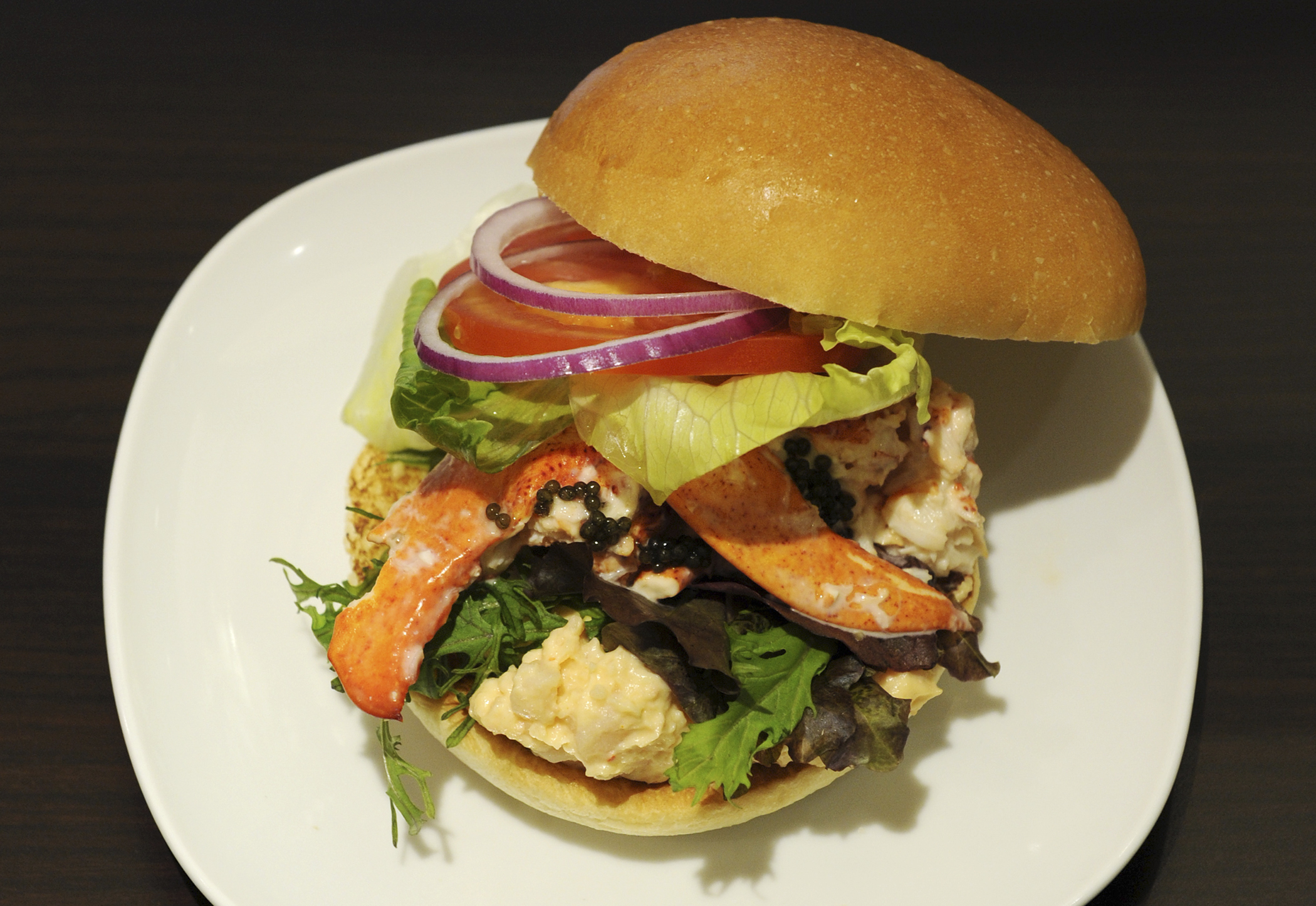 This picture shows the Lobster and Caviar burger featuring Canadian lobster and contains whole lobster pieces as well as a lobster salad made with a mustard mayonnaise as well as a sprinkle of caviar produced by Wendy's Japan as part of the campany's opening of their second restaurant in Roppongi, Tokyo on August 17, 2012. Wendy's Japan introduced two new burgers to their Japan Premium line of burgers which features fancy ingredients.
